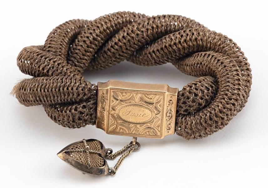 """Victorian hairwork bracelet with gold clasp engraved """"Susie"""" and heart-shaped drop pendant. Human hair, gold, interior circumference 4 in. Photograph courtesy Eldred's Auction Gallery, Dennis, Massachusetts."""
