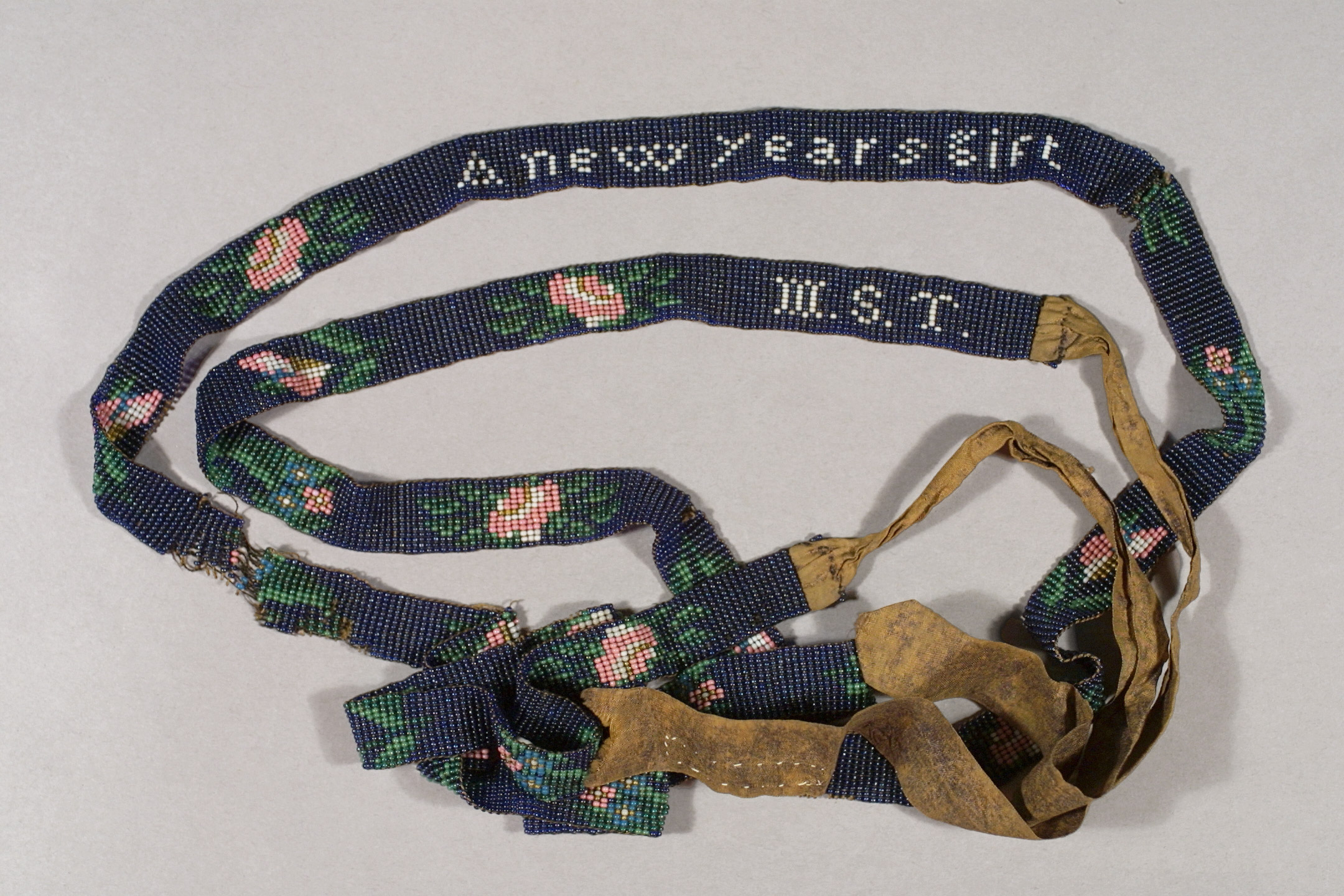 """Beaded chain with silk ribbon ends, inscribed in white beads """"A New Years gift / M.S.T,'' New England, ca. 1830–1840. Glass beads, silk, ½ in. wide. Historic New England, Gift of Mrs. Lucy Haskell Sturtevant, 1925.344A."""